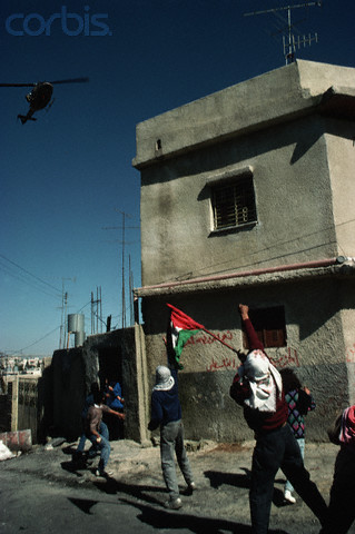 1988, West Bank --- Palestinian guerrillas throw rocks and make defiant gestures at a helicopter of the the occupying Isreali military forces. --- Image by Peter Turnley/CORBIS
