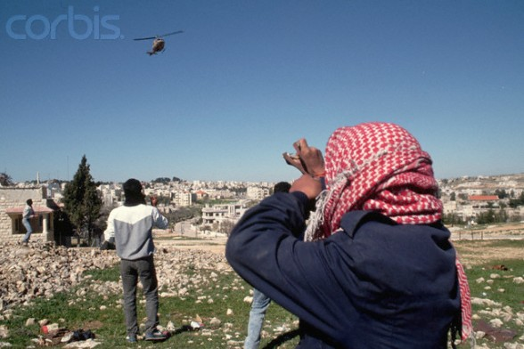 16 Mar 1988, West Bank --- Palestinians throw rocks at a helicopter of the occupying Israeli military forces. --- Image by  Peter Turnley/CORBIS