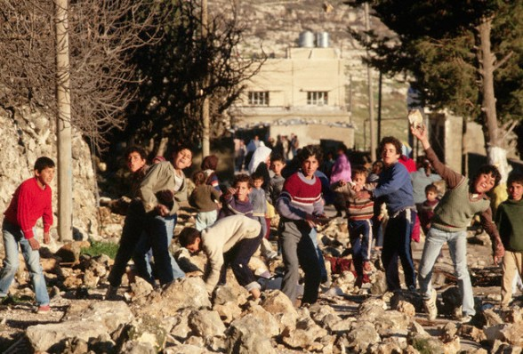 1988, West Bank --- Palestinian boys throw rocks at Israeli soldiers in the West Bank. --- Image by Peter Turnley/CORBIS
