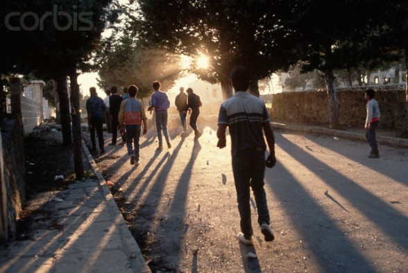 16 Mar 1988, West Bank --- Palestinian boys walk down a street littered with rocks, which they throw at the Israeli forces occupying the West Bank. --- Image by Peter Turnley/CORBIS