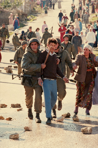 1988, West Bank --- Israeli soldiers escort an arrested man down a street littered with rocks thrown by Palestinian guerillas. --- Image by Peter Turnley/CORBIS