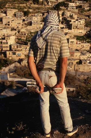 1988, West Bank --- Conflicts between Palestinians and the occupying Israeli military forces are a part of everyday life in the West Bank. Palestinian guerillas throw rocks and bottles at the Israelis. --- Image by Peter Turnley/CORBIS