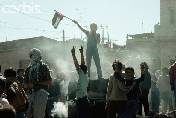 1988, West Bank --- Young Palestinian freedom fighters give the sign for liberation and wave a flag during a riot against the occupying Israeli soldiers. --- Image by Peter Turnley/CORBIS