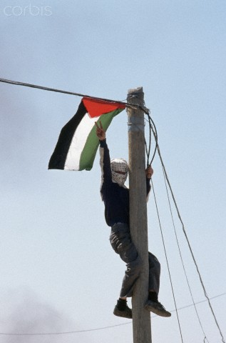 15 Mar 1988, Ramallah, West Bank --- A Palestinian boy gives the symbol for liberation as he climbs a pole. --- Image by Peter Turnley/CORBIS