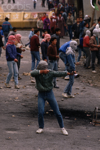 1988, West Bank --- Masked guerrillas fight in the Intifada, the Palestinian uprising against Israeli occupation. --- Image by Peter Turnley/CORBIS