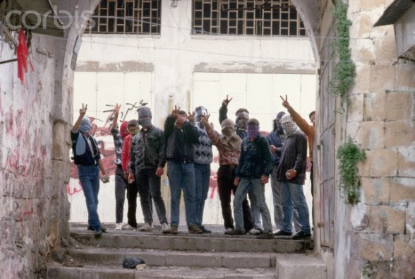 1988, Nablus, West Bank --- Masked Palestinian Guerrillas Giving Hand Signs --- Image by Peter Turnley/CORBIS
