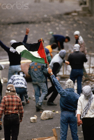 1988, Nablus, West Bank --- Masked Palestinians hold a flag and throw rocks at Israeli soldiers. --- Image by Peter Turnley/CORBIS