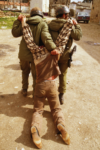1988, West Bank --- Israeli soldiers lead an arrested Palestinian man down a street during the Intifada. --- Image by Peter Turnley/CORBIS