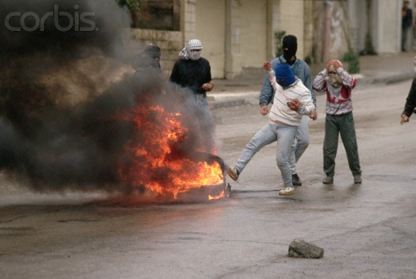 1988, West Bank --- Masked Palestinians stand by a fire blocking a street on the West Bank during the Intifada. --- Image by Peter Turnley/CORBIS