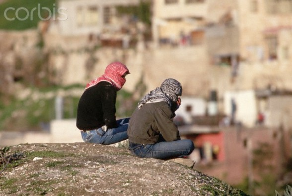 09 Feb 1988, East Jerusalem, West Bank --- Two young Palestinians look out over East Jerusalem, wearing kaffiyehs to mask their faces, like many stone throwers during the Intifada. --- Image by  Peter Turnley/CORBIS