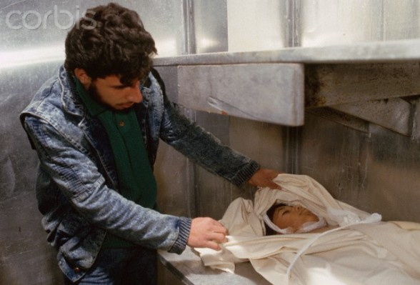 ca. February 1988, West Bank --- A man uncovers the face of a dead Israeli beating victim. --- Image by  Peter Turnley/CORBIS