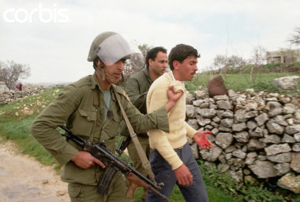 ca. March 1988, West Bank --- Two Israeli soldiers force a bleeding Palestinian man to walk with them down an unpaved road. --- Image by  Peter Turnley/CORBIS