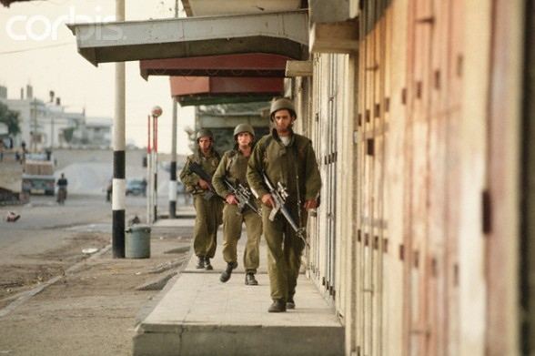 December 1993, Gaza, Gaza Strip --- Three armed Israeli soldiers patrol an urban street in Gaza. --- Image by Peter Turnley/CORBIS