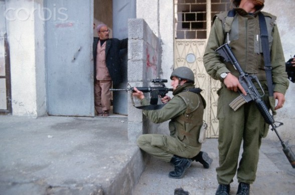 December 1993, Gaza, Gaza Strip --- A Palestinian man stands in his doorway watching the Israeli soldiers patrol the area. --- Image by  Peter Turnley/CORBIS