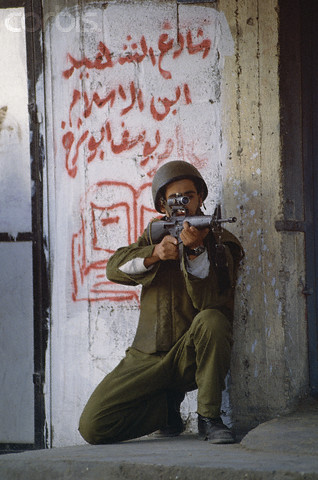 1993, Gaza, Gaza Strip --- An Israeli soldier aims his assault rifle during a 1993 Palestinian uprising in Gaza. --- Image by  Peter Turnley/CORBIS
