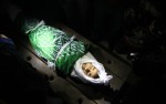 The body of Ramadan al-Zaalan, 12 years old, lies near mourners during his funeral in Gaza City on December 10, 2011. Zaalan was killed with his father Bahjat in an Israeli air strike on a civilian house in Gaza ( AFP PHOTO/MAHMUD HAMS