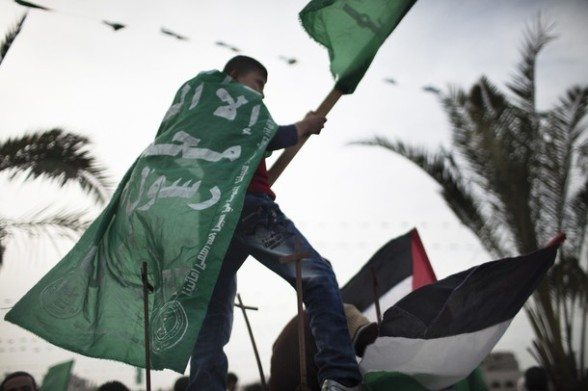 A Palestinian boy waves Hamas party flag