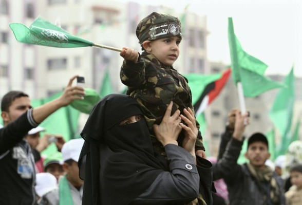 A Palestinian woman holds her son during a Hamas rally in Gaza City