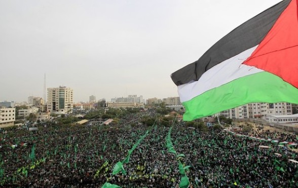 A Palestinian flag flutters as thousands