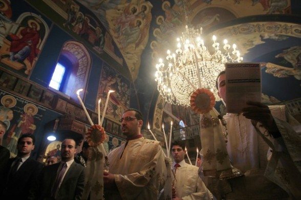 Palestinian Greek Orthodox Christians attend Christmas mass at the Orthodox Saint Porfirios church in Gaza City on January 7, 2012. The Orthodox Church celebrates Christmas and other religious holidays according to the Julian calendar, while other Christian churches have adopted the later Gregorian calendar.      AFP PHOTO/MAHMUD HAMS