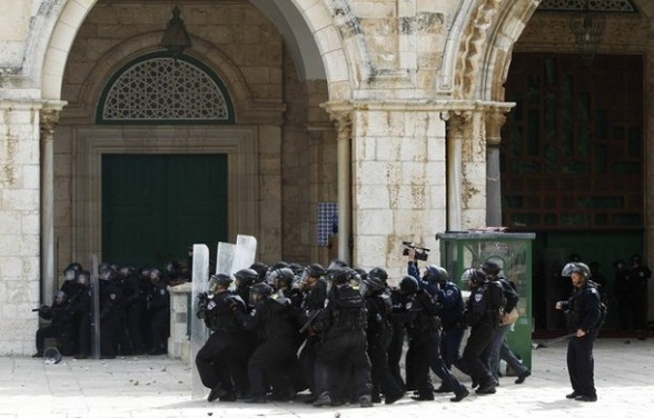 Israeli policemen take position behind their shields during clashes with Palestinian protesters on the compound known to Muslims as the Noble Sanctuary and to Jews as the Temple Mount in Jerusalem's Old City February 24, 2012. Israeli policemen stormed the compound on Friday following prayers, using stun grenades to disperse stone-throwing Palestinian protesters, some of whom then retreated into al-Aqsa mosque. Israeli police spokesperson said 11 policemen were lightly injured from stones and 4 protesters were arrested. REUTERS/Ammar Awad