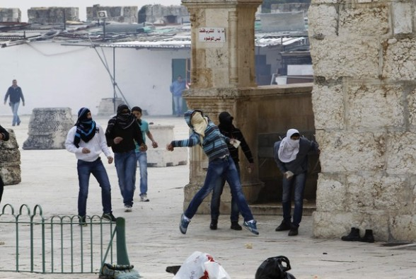 A Palestinian protester hurls stones during clashes with Israeli policemen on the compound known to Muslims as the Noble Sanctuary and to Jews as the Temple Mount in Jerusalem's Old City February 24, 2012. Israeli policemen stormed the compound on Friday following prayers, using stun grenades to disperse stone-throwing Palestinian protesters, some of whom then retreated into al-Aqsa mosque. Israeli police spokesperson said 11 policemen were lightly injured from stones and 4 protesters were arrested. REUTERS/Ammar Awad
