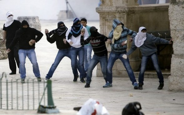 Palestinian protesters prepare to throw stones during clashes with Israeli police at the flashpoint Al-Aqsa mosque compound in Jerusalem's old city on February 24, 2012. The clashes followed nearly a week of unrest at the walled complex, which is one of the most sensitive places in the Middle East. AFP PHOTO/STR