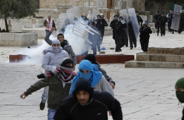 Palestinian protesters run away from Israeli policemen during clashes on the compound known to Muslims as the Noble Sanctuary and to Jews as the Temple Mount in Jerusalem's Old City February 24, 2012. Israeli policemen stormed the compound on Friday following prayers, using stun grenades to disperse stone-throwing Palestinian protesters, some of whom then retreated into al-Aqsa mosque. Israeli police spokesperson said 11 policemen were lightly injured from stones and 4 protesters were arrested. REUTERS/Ammar Awad