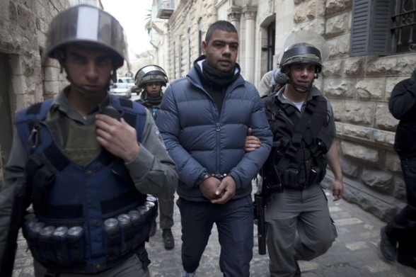 Israeli border policemen escort a Palestinian man after he was arrested in the old city of Jerusalem on February 24, 2012 following clashes between Israeli police and