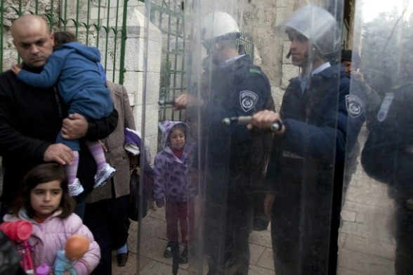 A Palestinian family walks past Israeli border policemen standing behind shields in the old city of Jerusalem on February 24, 2012 following clashes between Israeli police and