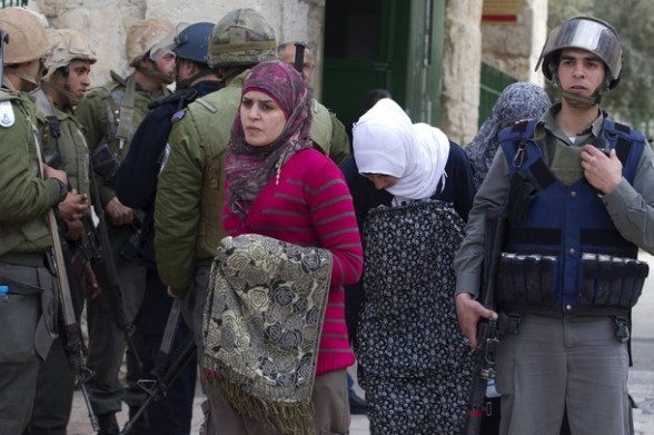 Palestinian women walk past Israeli border policemen in the old city of Jerusalem on February 24, 2012 following clashes between Israeli police and