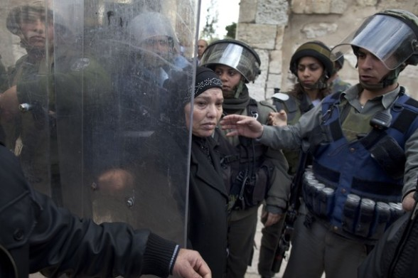 A Palestinian woman walks between Israeli border policemen in the old city of Jerusalem on February 24, 2012 after clashes broke out between Israeli police and