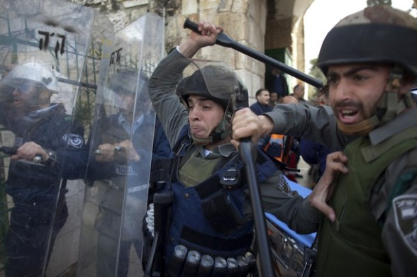 Israeli border policemen raise their batons to disperse Palestinian protesters in the old city of Jerusalem on February 24, 2012 as clashes broke out between Israeli police and