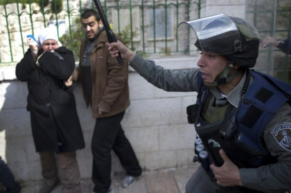 An Israeli border policeman raises his baton to disperse Palestinian protesters in the old city of Jerusalem on February 24, 2012 as clashes broke out between Israeli police and