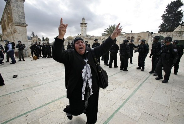 A Palestinian woman shouts as she runs past Israeli police during clashes at the flashpoint Al-Aqsa mosque compound in Jerusalem's old city on February 24, 2012. Clashes briefly broke out between Israeli police and