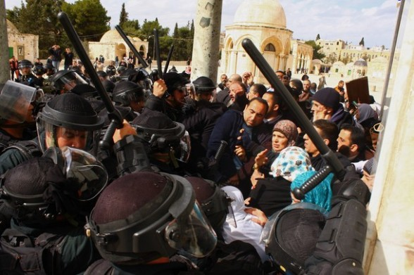 Palestinians gather as Israeli policemen stand guard at the entrance to the Dome of the Rock at the flashpoint Al-Aqsa mosque compound in Jerusalem's old city on February 24, 2012. Clashes briefly broke out between Israeli police and