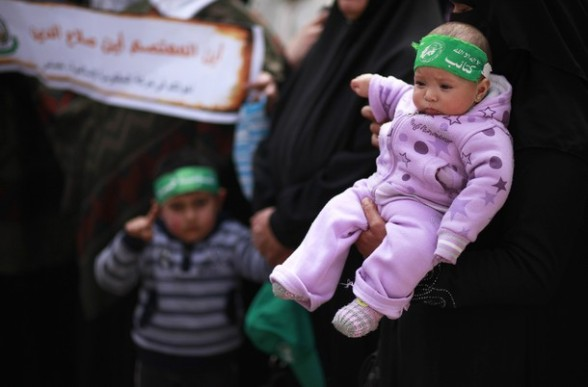 A Palestinian woman holds her daughter during a rally organised by the Hamas movement in Gaza City, to show solidarity with the al-Aqsa Mosque in Jerusalem February 26, 2012. REUTERS/Suhaib Salem
