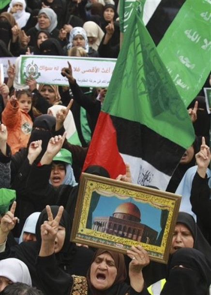 Palestinian women, holding green Islamic flags and a Palestinian flag, attend a rally in solidarity with Jerusalem, in Gaza City, Sunday, Feb. 26, 2012, following the clashes erupted between Palestinians and Israeli police at the Al Aqsa Mosque compound during the weekend. Dome of the Rock Mosque shown in picture. (AP photo/Hatem Moussa)