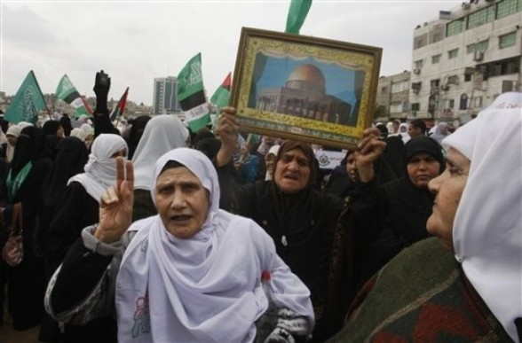 Palestinian women attend a rally in solidarity with Jerusalem, in Gaza City, Sunday, Feb. 26, 2012, following the clashes erupted between Palestinians and Israeli police at the Al Aqsa Mosque compound during the weekend. Dome of the Rock Mosque shown in picture. (AP photo/Hatem Moussa)