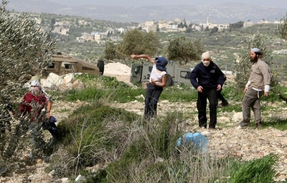Archive photo: Masked Israeli settlers from the Havat Gilad settlement throw stones at Palestinian villagers near Farata, east of the West Bank ciy of Qalqilya, on February 28, 2012. AFP PHOTO/JAAFAR ASHTIYEH
