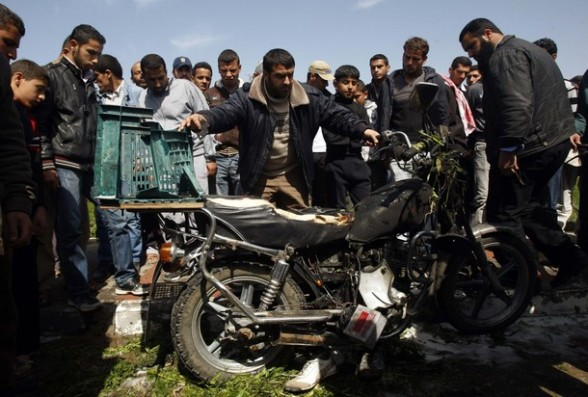Palestinians inspect a motorcycle that was hit in an Israeli air strike in Khan Younis in the southern Gaza Strip March 10, 2012. Israel killed four Gaza militants on Saturday as violence sparked by the death of a militant leader a day earlier escalated with gunmen firing more than 90 rockets at Israel, injuring four people, Israeli and Palestinian officials said. REUTERS/ Ibraheem Abu Mustafa
