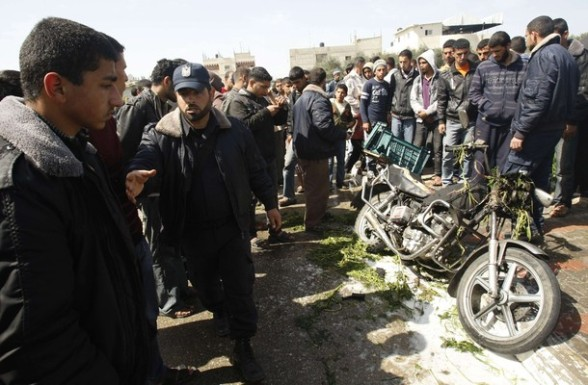 A Hamas policeman takes charge as Palestinians look at a motorcycle that was hit in an Israeli air strike in Khan Younis in the southern Gaza Strip March 10, 2012. Israel killed four Gaza militants on Saturday as violence sparked by the death of a militant leader a day earlier escalated with gunmen firing more than 90 rockets at Israel, injuring four people, Israeli and Palestinian officials said. REUTERS/ Ibraheem Abu Mustafa