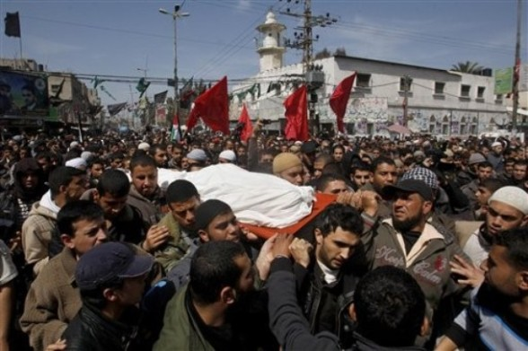Palestinian carry the body of Zuhair al-Qaissi, commander of the armed wing of the Popular Resistance Committees (PRC), during his funeral in Rafah, southern Gaza Strip, Saturday, March 10, 2012. The worst exchange of strikes between Israel and the Gaza Strip so far this year entered its second day on Saturday, as Israeli aircraft carried out raids that have so far killed 14 militants according to a Palestinian count (AP Photo/Hatem Moussa)