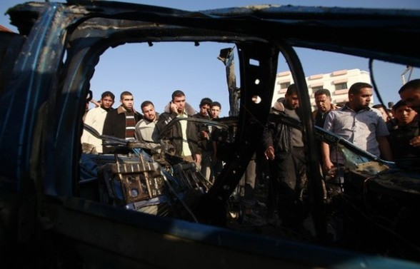 Palestinians look at the remains of a vehicle after it exploded in Gaza City March 9, 2012. Israel killed the leader of a Palestinian militant faction on Friday in a targeted attack on the car in the Gaza Strip, an Israeli official said. A second man also died in the blast, and a third was injured. The attack came shortly after two rockets were fired at Israel from the coastal territory, causing no damage or injury. REUTERS/Suhaib Salem