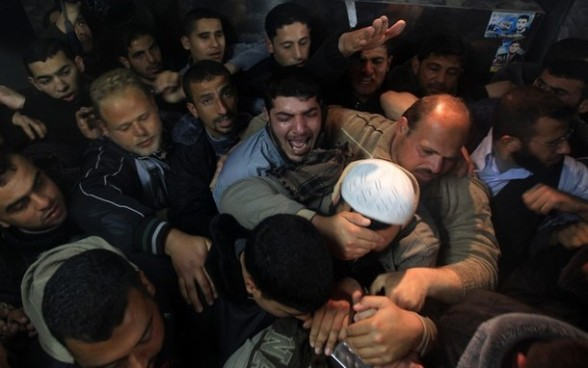 Palestinians mourn in a hospital after two militants of the Al Quds Brigades, the military arm of Islamic Jihad, were killed in a second Israeli air strike in Gaza City on March 9, 2012, bringing the number of Palestinians killed in a day of cross-boarder fighting to four. The two strikes came in response to two waves of Palestinian mortar fire into southern Israel, in which no casualties were reported . AFP PHOTO/ MAHMUD HAMS
