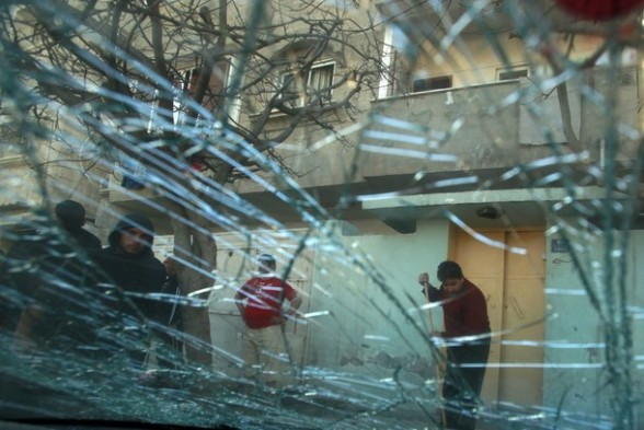 A Palestinian man is seen through a broken car window as he cleans the scene after another car nearby exploded in Gaza City March 9, 2012. Israel killed the leader of a Palestinian militant faction on Friday in a targeted attack on the car in the Gaza Strip, an Israeli official said. A second man also died in the blast, and a third was injured. The attack came shortly after two rockets were fired at Israel from the coastal territory, causing no damage or injury. REUTERS/Suhaib Salem