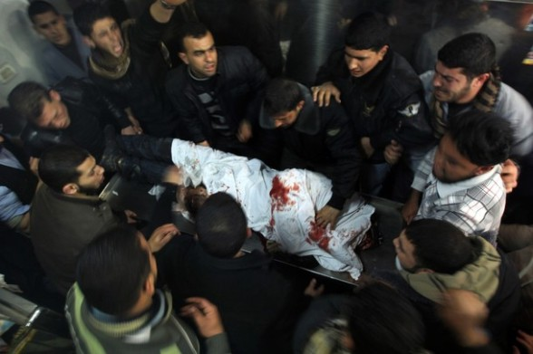Palestinians mourn over the body of one of two militants of the Al Quds Brigades, the military arm of Islamic Jihad, after they were killed in a second Israeli air strike in Gaza City on March 9, 2012, bringing the number of Palestinians killed in a day of cross-boarder fighting to four. The two strikes came in response to two waves of Palestinian mortar fire into southern Israel, in which no casualties were reported . AFP PHOTO/ MAHMUD HAMS