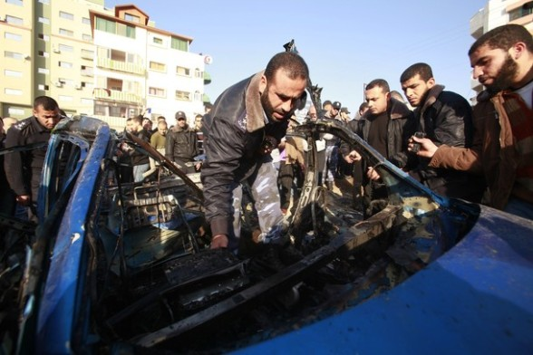 Hamas policemen inspect the remains of a vehicle after it exploded in Gaza City March 9, 2012. Israel killed the leader of a Palestinian militant faction on Friday in a targeted attack on the car in the Gaza Strip, an Israeli official said. A second man also died in the blast, and a third was injured. The attack came shortly after two rockets were fired at Israel from the coastal territory, causing no damage or injury. REUTERS/ Suhaib Salem