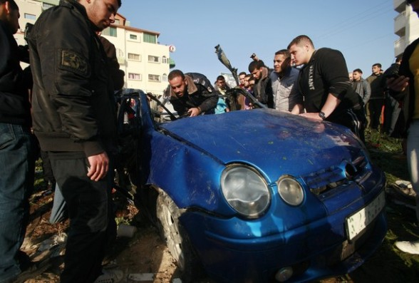 A Hamas policeman inspects the remains of a vehicle after it exploded in Gaza City March 9, 2012. Israel killed the leader of a Palestinian militant faction on Friday in a targeted attack on the car in the Gaza Strip, an Israeli official said. A second man also died in the blast, and a third was injured. The attack came shortly after two rockets were fired at Israel from the coastal territory, causing no damage or injury. REUTERS/ Suhaib Salem