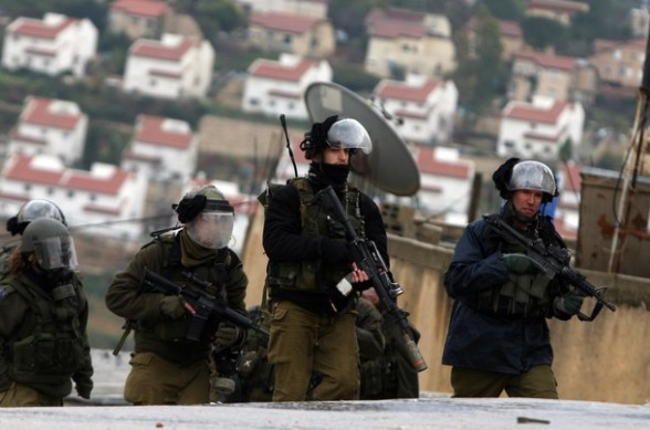 Israeli soldiers march during clashes with Palestinian and foreign activists in the West Bank village of Nabi Saleh, near Ramallah, on March 16, 2012 following a protest against Palestinian land confiscation to build the Jewish settlement Hallamish nearby. AFP PHOTO/ABBAS MOMANI